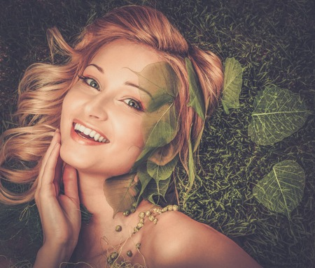 Dreaming young woman lying on a fresh spring grass photo