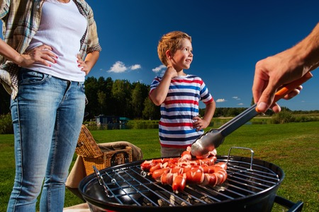 meat on grill: Young family preparing sausages on a grill outdoors