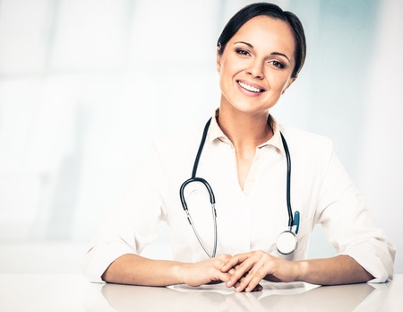 medicaments: Smiling doctor woman behind table taking notes