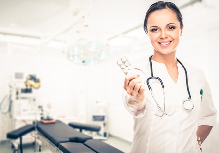 Doctor woman holding pills in surgery room interior photo