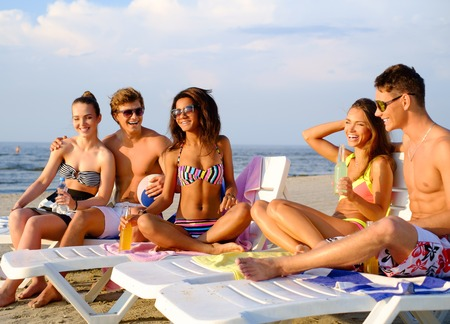 deck chairs: Group of multi ethnic friends with drinks relaxing on a beach Stock Photo