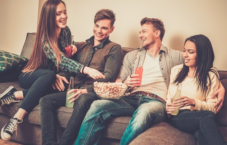 Group of cheerful students with drinks and popcorn in home interior photo