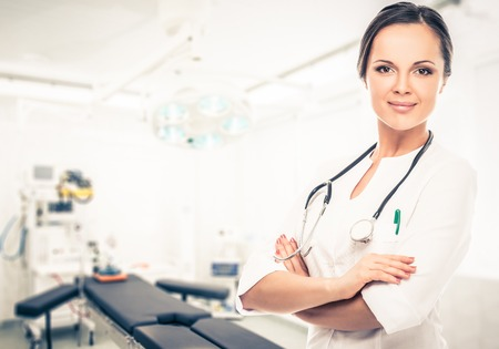 medicaments: Positive brunette doctor woman in surgery room interior