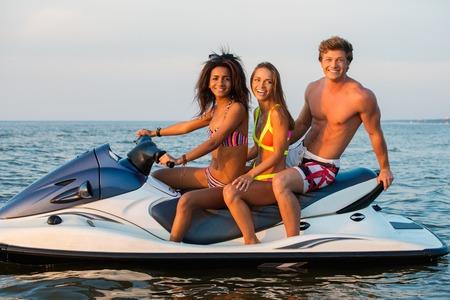moto acuatica: Multinacionales amigos sentados en una moto de agua Foto de archivo