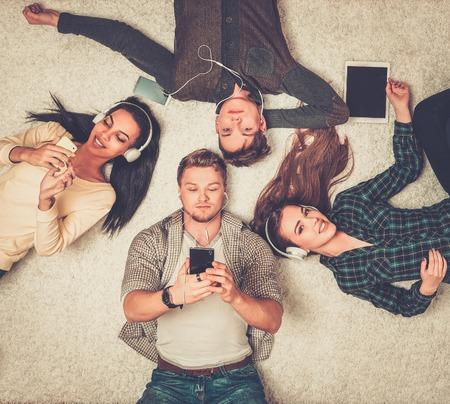 personas felices: Amigos multirraciales felices descansando sobre una alfombra con los gadgets