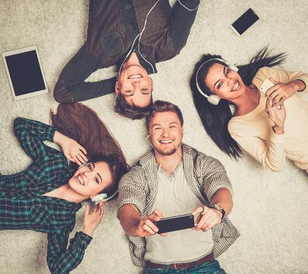 descansando: Amigos multirraciales felices descansando sobre una alfombra con los gadgets