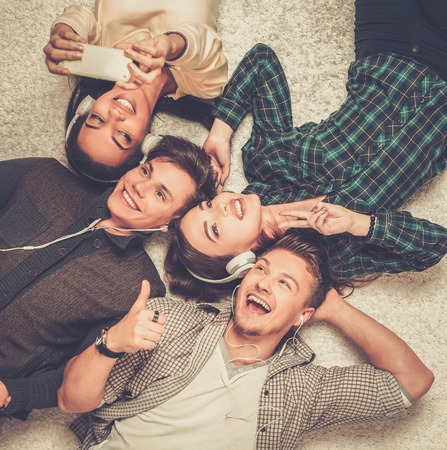 diversity people: Happy multiracial friends relaxing on a carpet with gadgets Stock Photo