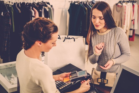 boutique shop: Happy woman customer paying with credit card in fashion showroom Stock Photo