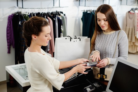 customer assistant: Happy woman customer paying with credit card in fashion showroom Stock Photo