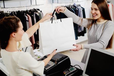 cash: Cliente feliz con bolsa de compras en el showroom de moda Foto de archivo
