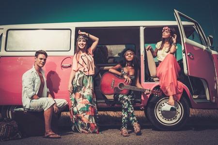 juventud: Amigos hippies multi�tnicos con la guitarra en un viaje por carretera