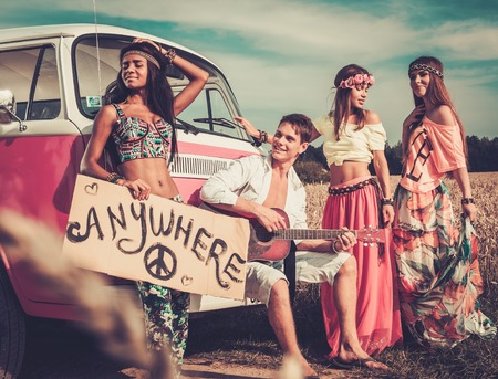 hippie: Multinational hippie hitchhikers with guitar and luggage on a road