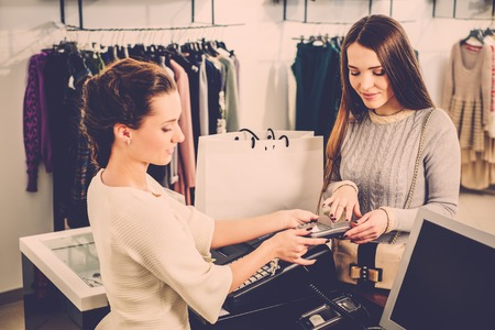 cash desk: Happy woman customer paying with credit card in fashion showroom Stock Photo