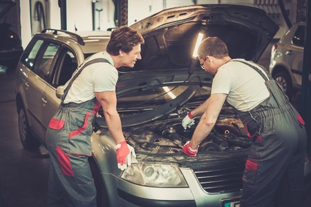 two car garage: Two mechanics fixing car in a workshop