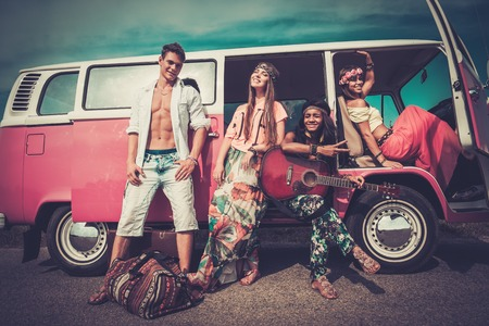 Multi-ethnic hippie friends with guitar on a road trip photo