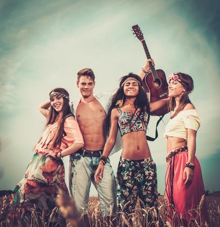 mujer hippie: Amigos hippies multinacionales con la guitarra en un campo de trigo