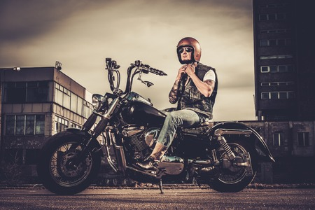 helmet seat: Tattooed biker and his bobber style motorcycle on a city streets