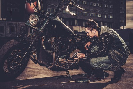 cruiser bike: Biker repairing his custom motorcycle bobber on a road