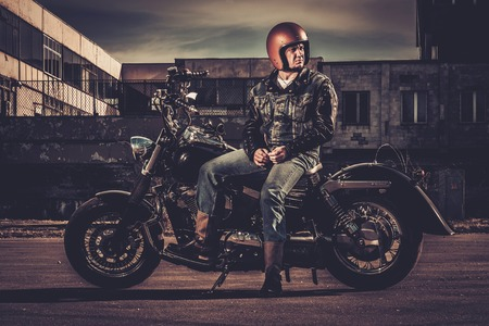 bobber: Biker and his bobber style motorcycle on a city streets
