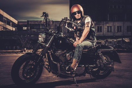 cruiser bike: Biker and his bobber style motorcycle on a city streets