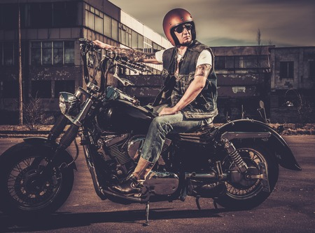 helmet seat: Biker and his bobber style motorcycle on a city streets