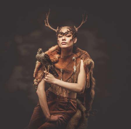 Woman shaman in ritual garment with hawk photo