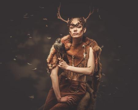 animal ritual: Woman shaman in ritual garment with hawk