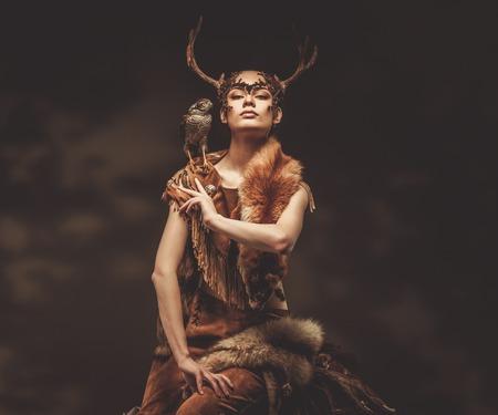 Mujer chamán en prenda ritual con halcón