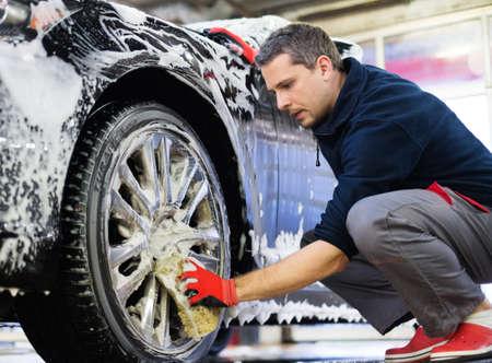 lavado: Llantas de aleaci�n Hombre trabajador de lavado del coche en un t�nel de lavado