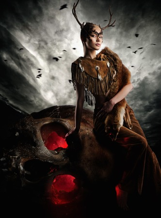 Woman shaman in ritual garment siting on skull photo