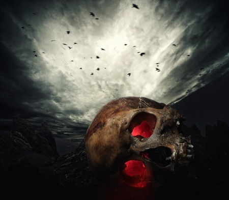 Human skull with glowing eyes against stormy sky photo
