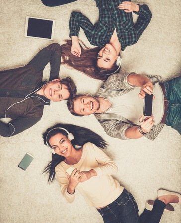 Happy multiracial friends relaxing on a carpet with gadgets Stock Photo
