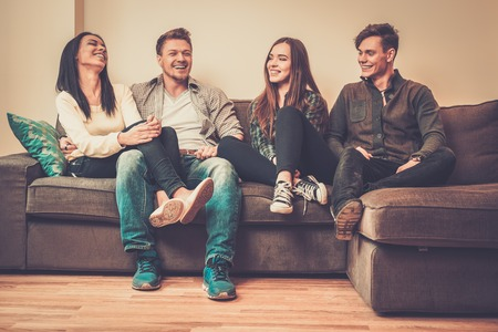 condos: Cheerful multi-ethnic friends sitting on a sofa