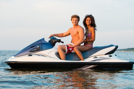 jet ski: Multinacional pareja sentada en una moto de agua