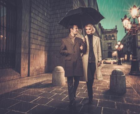 uomo sotto la pioggia: Coppia elegante con ombrello a piedi all'aperto sotto la pioggia