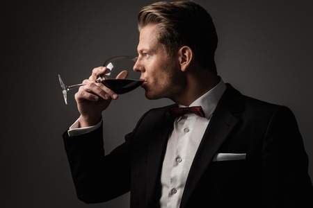 drunk party: Confident sharp dressed man with glass of wine