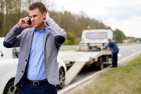 camión: El hombre que llama mientras grúa recoger su coche roto Foto de archivo