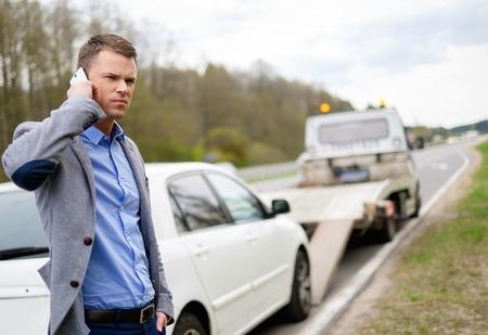 camion: El hombre que llama mientras gr�a recoger su coche roto Foto de archivo
