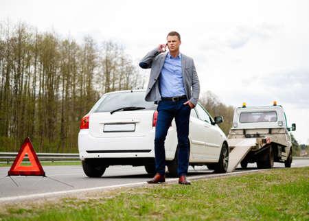 cami�n de reparto: El hombre que llama mientras gr�a recoger su coche roto Foto de archivo