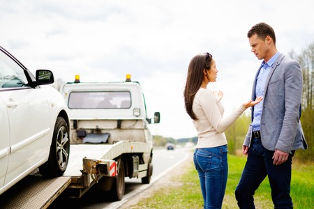 car breakdown: Couple near tow-truck picking up broken car Stock Photo