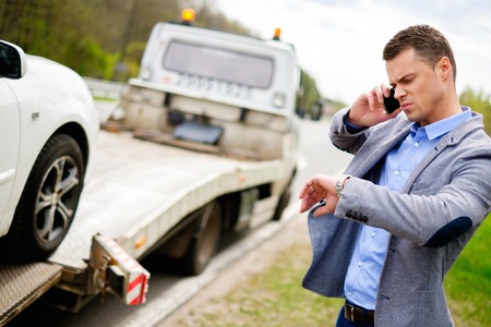towing: Man calling while tow truck picking up his broken car