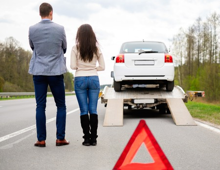 damaged car: Couple near tow-truck picking up broken car Stock Photo