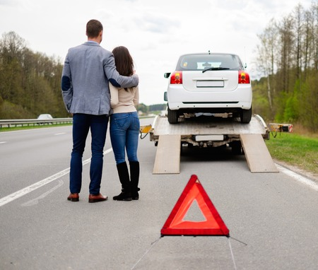 trailer truck: Couple near tow-truck picking up broken car Stock Photo