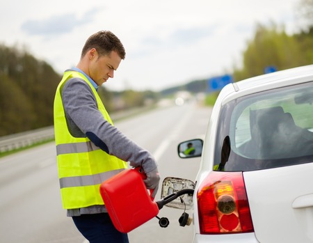 Man refuelling her car on a highway roadside
