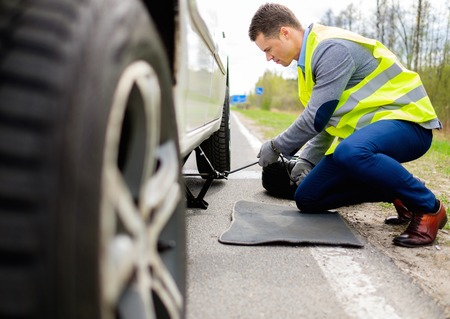 car tire: Man changing wheel on a roadside