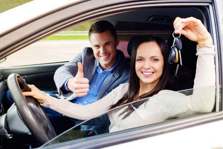 woman driving car: Happy driving student with a car keys