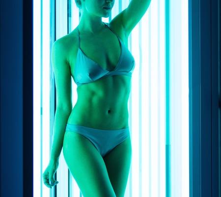 solarium: Young woman sunbathing in solarium