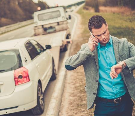damaged car: Man calling while tow truck picking up his broken car