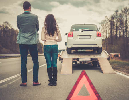 tow: Couple near tow-truck picking up broken car Stock Photo