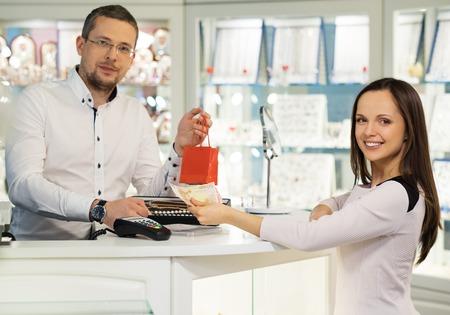 pagando: Mujer que paga con dinero en efectivo en la tienda de joyas